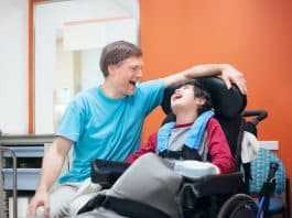 Disabled little boy in wheelchair talking with father in hospital room
