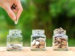 Conceptual hand putting coins into bottle on nature background,Business investment growth concept